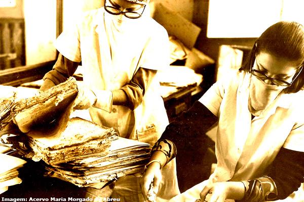 Na foto, Ana Lúcia di Lourenzo e Lia Carolina Prado Alves. higienizam os documentos taubateanos.